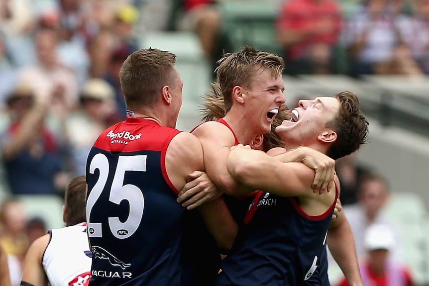 Three Melbourne players jump and hug each other while smiling