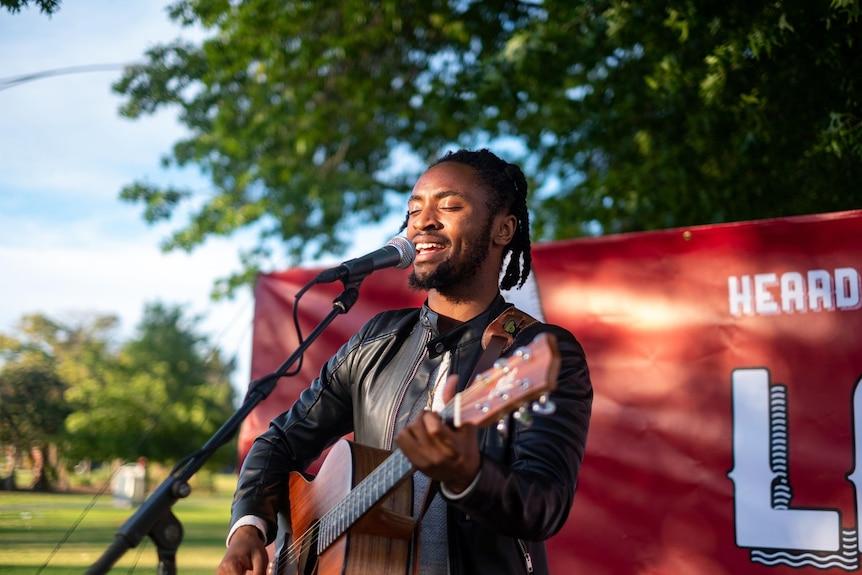 Eimable Manirakiza closes his eyes as he sings and plays guitar at a gig.