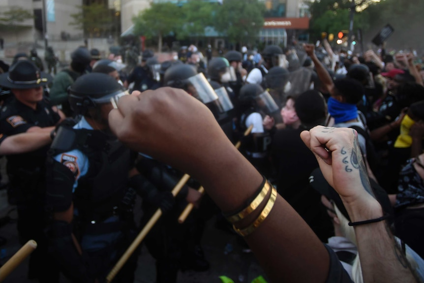 Two fists raised in the air with riot police advancing in the background.