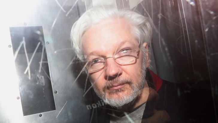 Julian Assange looks to the camera as he is photographed from behind glass with graffiti etched into it. His grey hair is back.