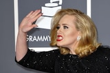 Adele plays up for the cameras on the Grammys red carpet