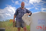 Townsville man Dave Dudley holds a piece of plastic waste, he stands in front of illegal dumping signs erected in a paddock.