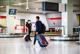 Two male passengers wheeling suitcases in an airport terminal.