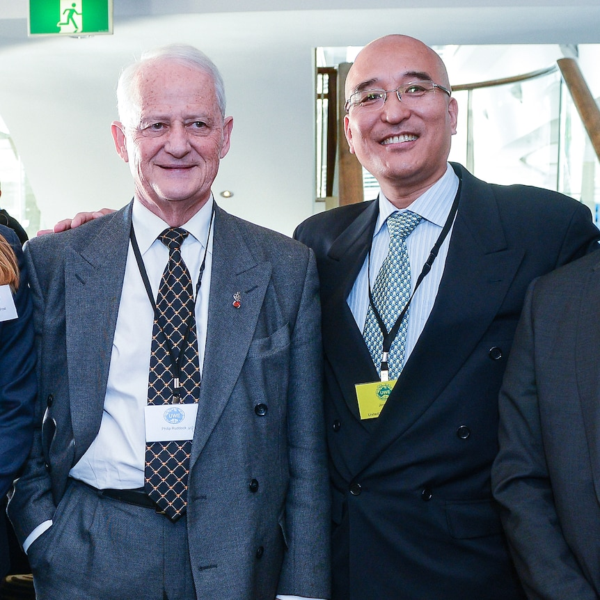Jimmy puts arm around Philip Ruddock in a conference photo.
