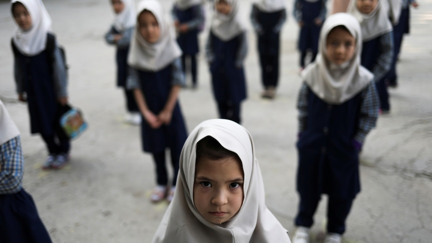Afghan school girls stand outside wearing uniforms and headscarves.