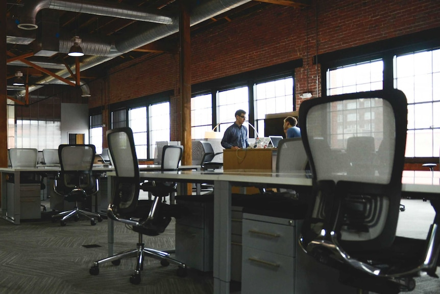Chairs and desks set up in an open plan layout in a converted warehouse.