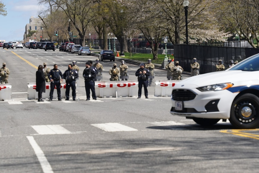 Police and army line the street behind a police car.