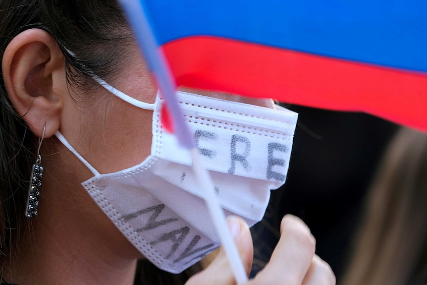 """A woman wears a facemask that says """"free Navalny"""" on it, she is holding a Russian flag."""