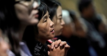 A woman clasps her hands together as she prays.
