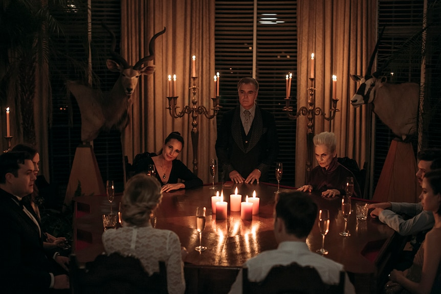 Henry Czerny stands between seated Andie MacDowell and Nicky Guadagni at round table in Gothic style room lit up by candles.