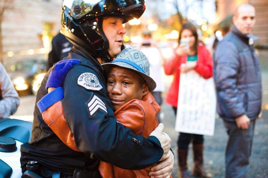 A white police officer waring a helmet embraces a young black boy who has tears running down his face.