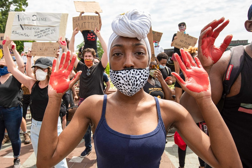A woman in a face mask holding her hands up with red paint on her palms
