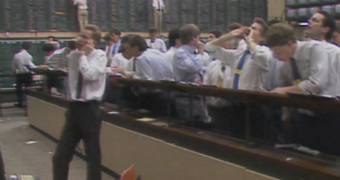 A man speaks on the phone inside wall st while other brokers look on in shock