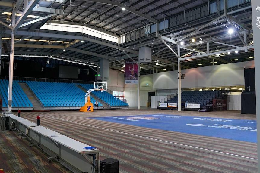 A pop-up basketball court under construction with a carpet floor inside an old Bunnings Warehouse.