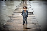 A Pakistani child stands on a wooden bridge surrounded by floodwaters