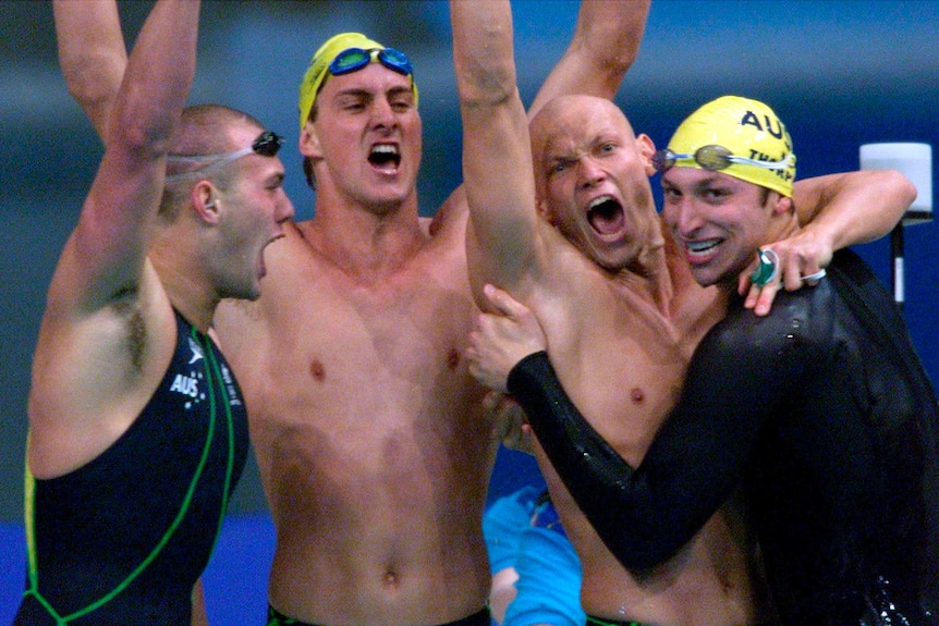Swimming relay team punches the air and roars in triumph on the blocks after winning Olympic gold.