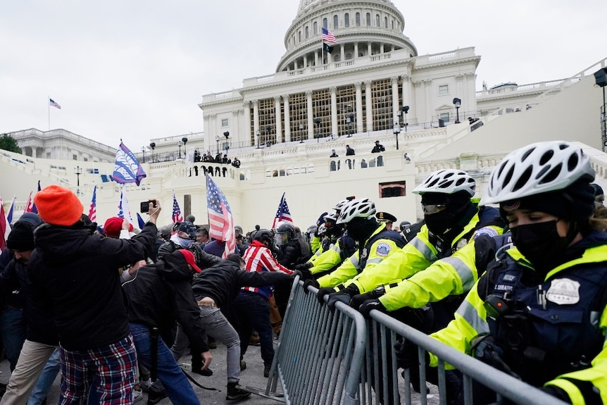 Trump supporters try to break through a police barrier on the US Capitol
