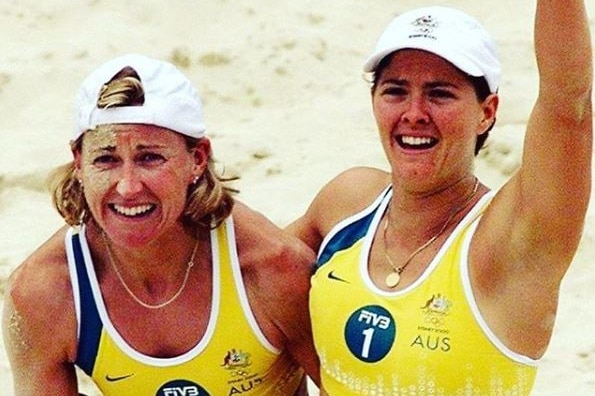 Two women wearing yellow and green bikinis embrace on the sand.