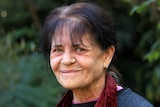 An older woman with dark hair looks side-on to the camera, smiling slightly.