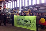 Forest activists hold a sign inside Ta Ann's Smithton sawmill in 2012.