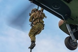 A soldier in camouflage uniform rappels from a helicopter.