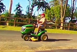 A man on a ride-on lawnmower with a beer in hand drive down a street in Cairns.
