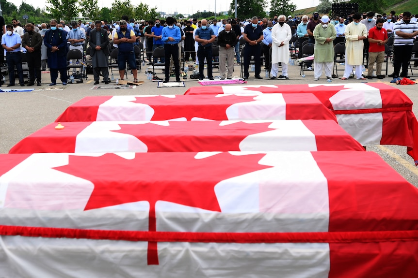 A row of mourners bow their heads and pray as four coffins are draped in the red and white Canadian flag.