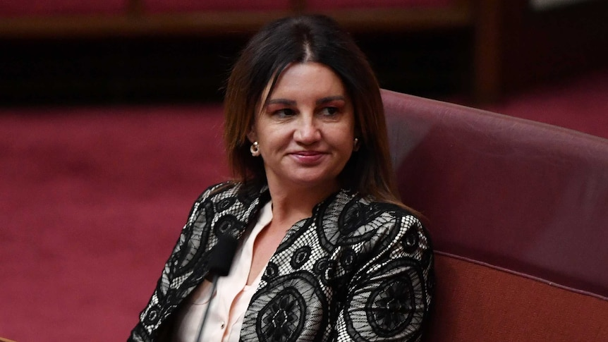 Senator Jacqui Lambie sits in the Senate and looks to the side.