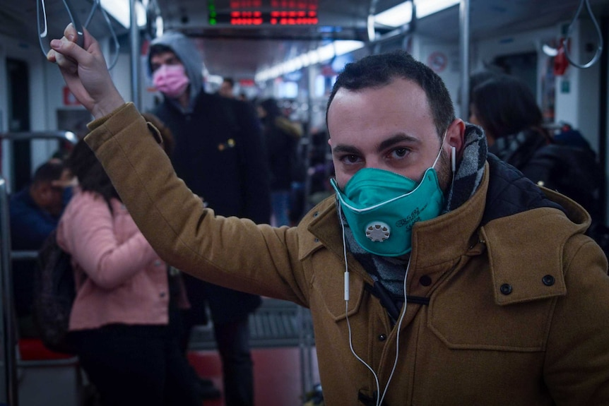 A commuter on Milan's underground railway wears a mask while listening to music with earphones.