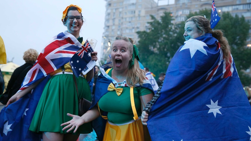 3 girls wearing green and gold and australian flag capes arrive at the exhibition centre in Kiev