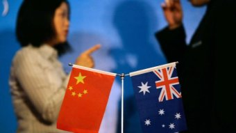 Two people talk in front of the Chinese and Australian flags.