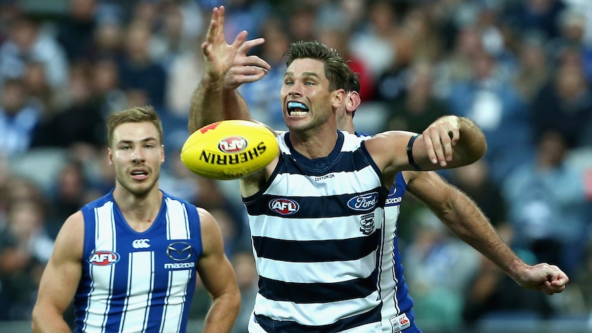 A Geelong AFL player tries to catch the ball in front of a North Melbourne opponent.