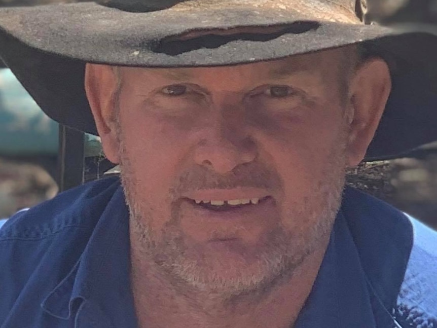 A farmer in a blue work shirt and a battered hat.