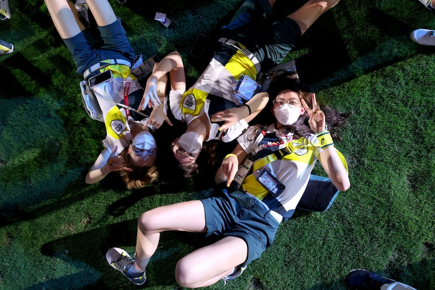 three athletes dressed in australia's olympic formal uniform lie on the ground throwing peace signs and shakkas