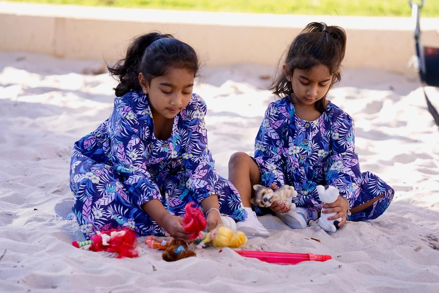 Two young sisters wearing floral dresses have heads down as they sit and play in a sandpit
