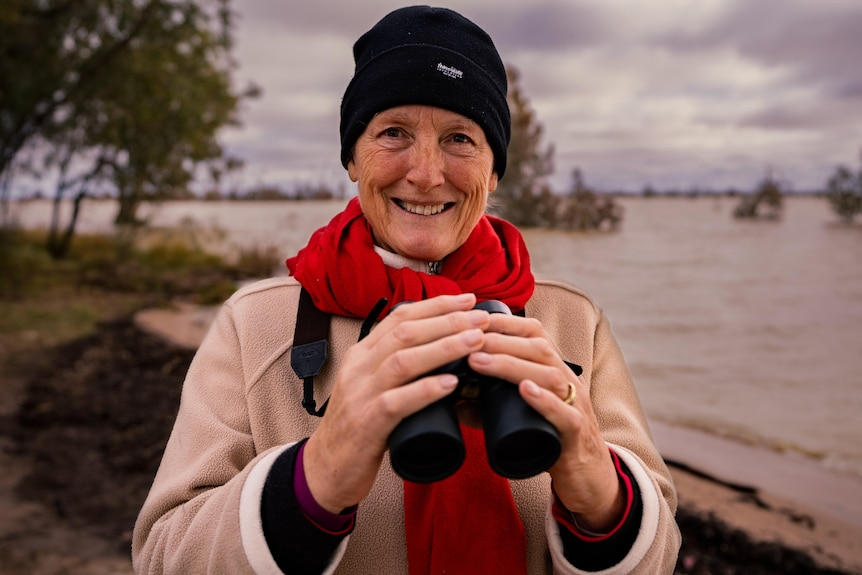 a woman with binoculars with water behind