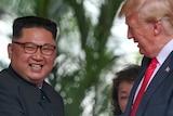 Donald Trump gestures as he talks to smiling Kim Jong-un.