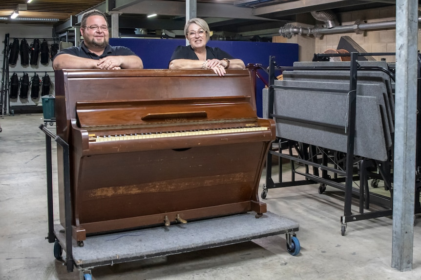 an old upright piano with two people standing smiling behind it