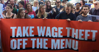 Workers hold take wage theft off the menu sign