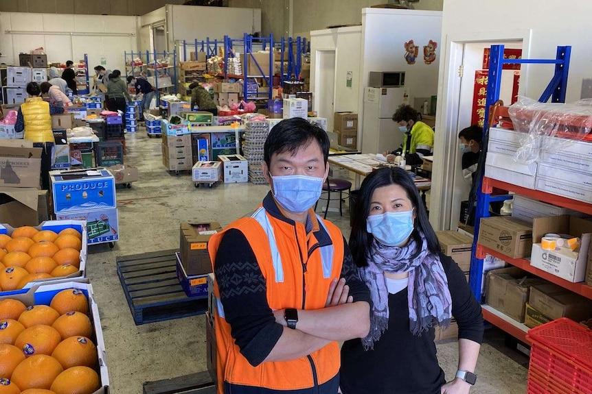 巨大的食品储存库内,一对身穿工作服的年轻夫妇站在镜头前拍照。
