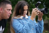 A man leans over a teenage girl's shoulder, while she concentrates on looking into a camera she's holding