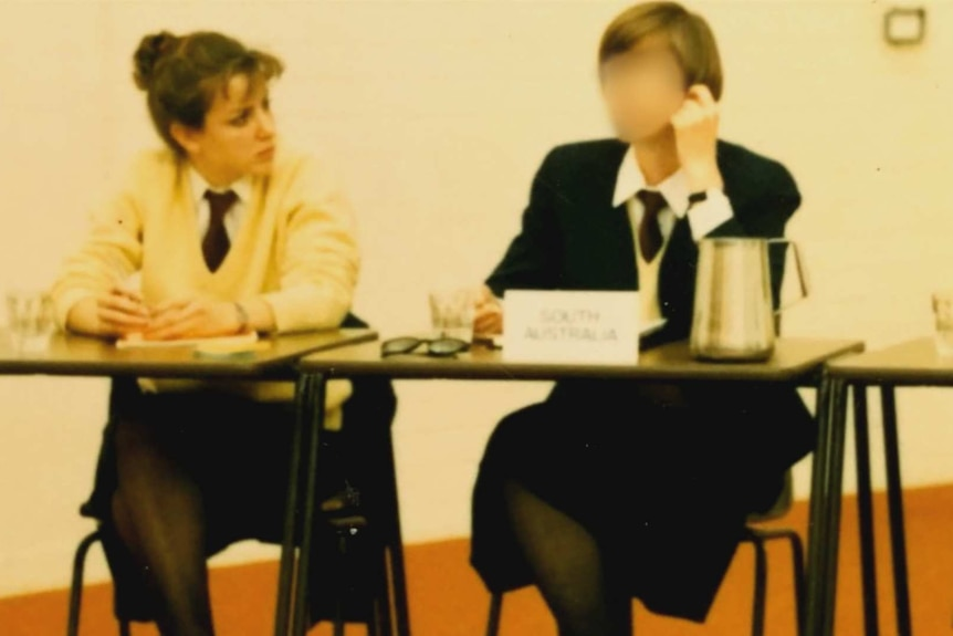 Jo Dyer and the woman sit at a desk in their school uniforms