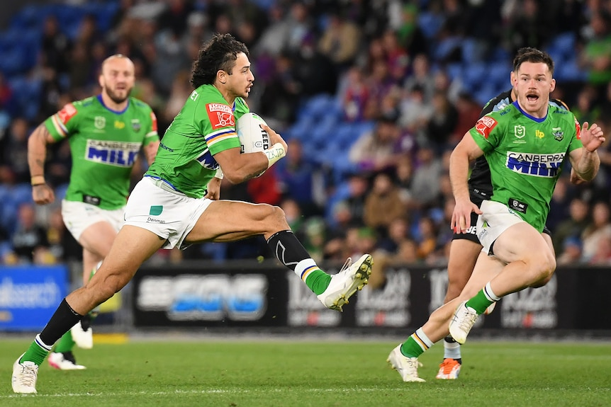 A Canberra Raiders NRL player strides out as he runs with the ball against Cronulla.