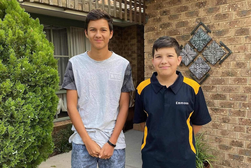 Two boys outside a house smile at the camera.