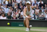 Ash Barty lunges forward to make a backhand return as the ball bounces low off the grass in the Wimbledon final.