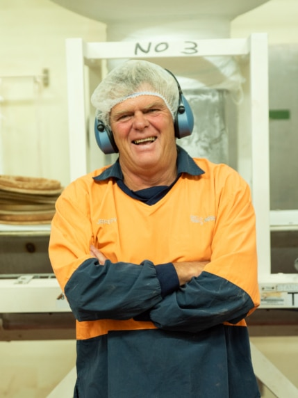 Man in hairnet and overalls laughing
