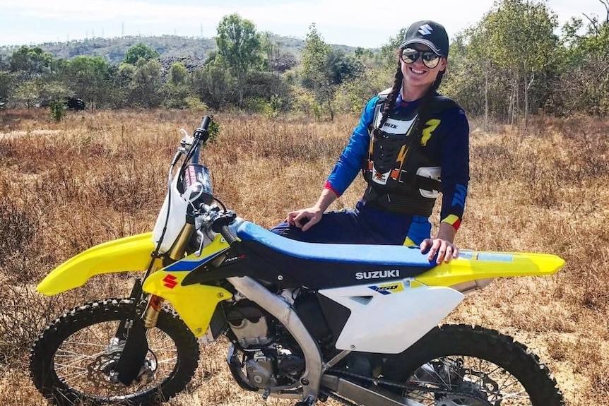 Girl with long dark hair wearing hat and sunglasses stands behind yellow motorbike in dry bushland.