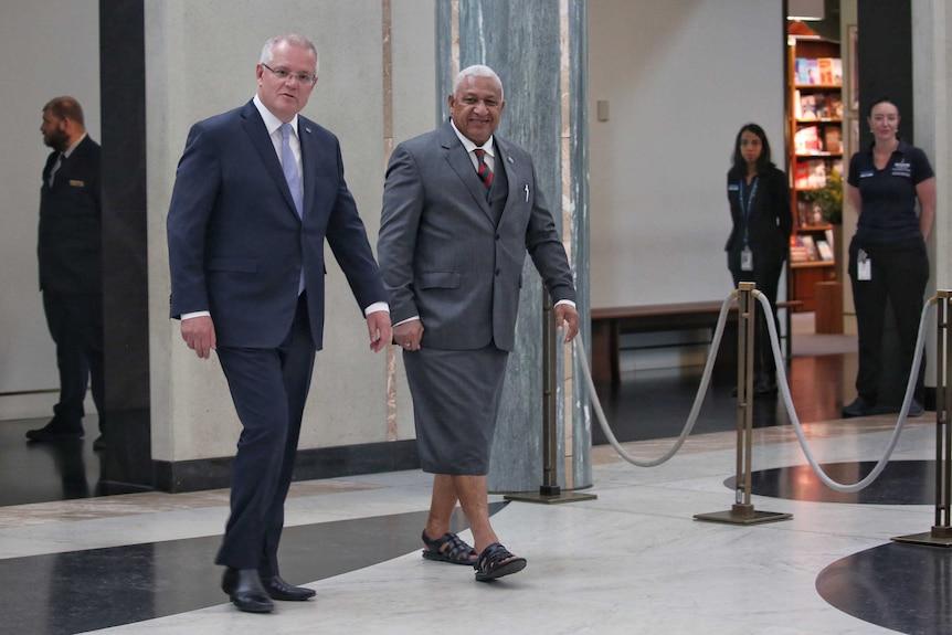 Australian Prime Minister Scott Morrison walks alongside Fijian Prime Minister Frank Bainimarama