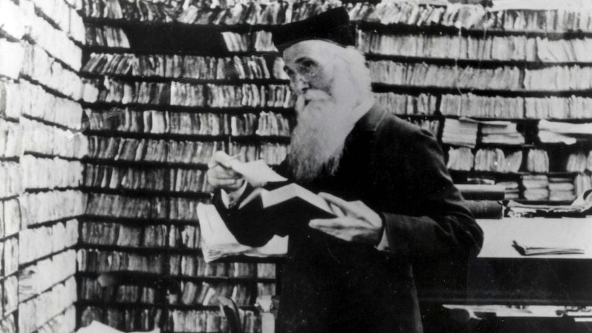 Black and white photo of a man with long beard and glasses, holding a book and surrounded by shelves of many tiny paper slips.