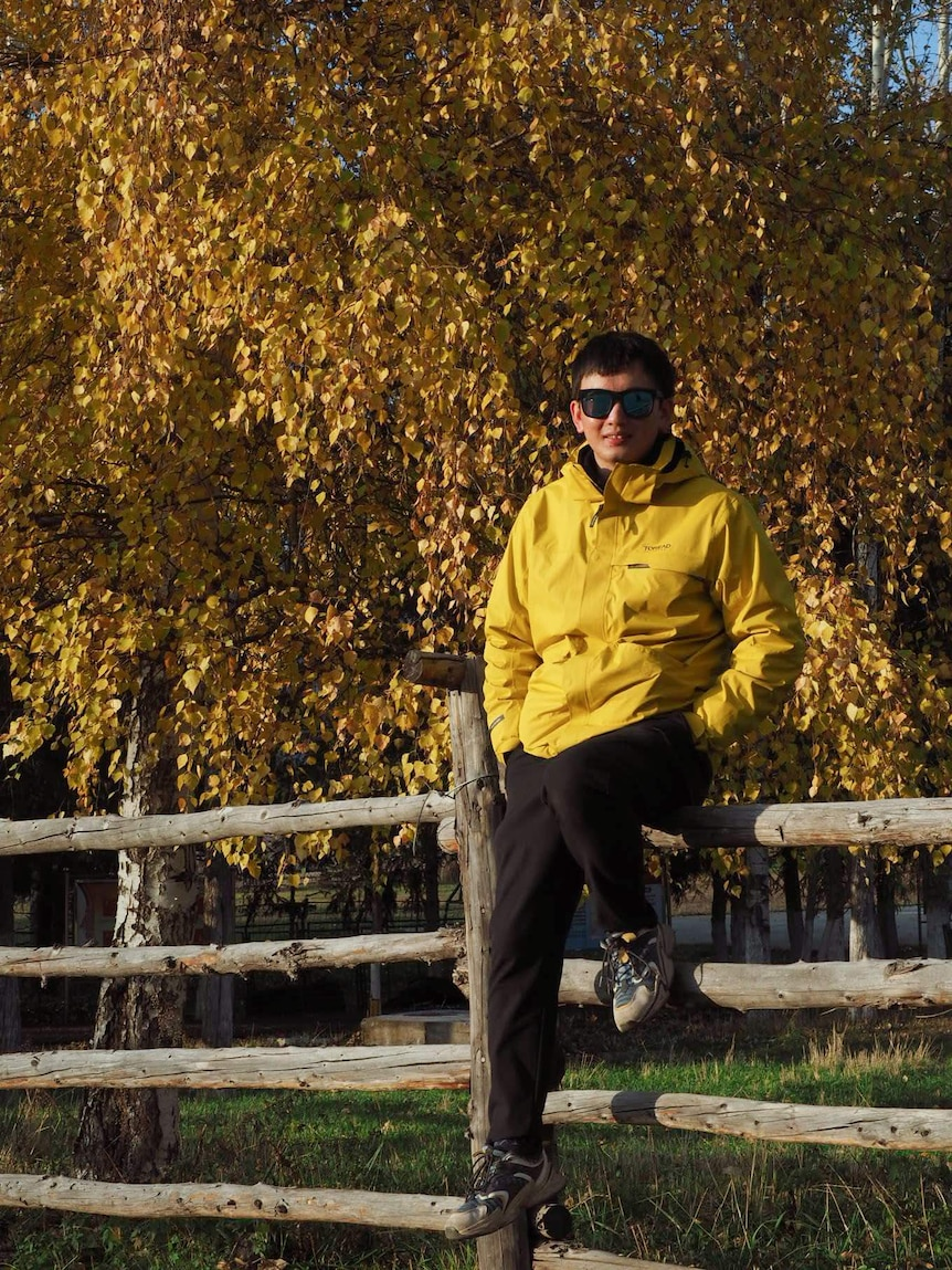 Shengwei Ye sits on a wooden fence with a large tree of yellow leaves behind him.